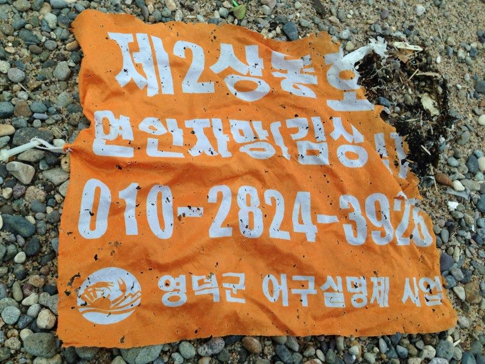 韓国からの漂着物「漁師さんの連絡先の入った旗」