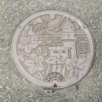 香住のマンホールの図柄は「サツキ」と「余部埼灯台」と「日本海」と「カニマーク」